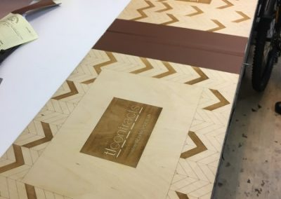A very large and specialist timber engraved case in the process of completion, accompanied with a brown material to secure the spine